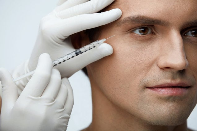 75361604 - face injection. closeup of beautician doing hyaluronic acid injection on handsome man skin. portrait of young male receiving facial beauty treatment, filler injections. cosmetology. high resolution